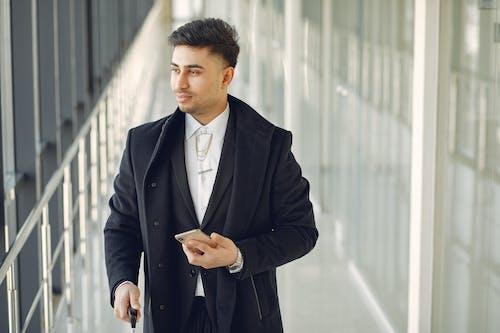 Pensive ethnic man in formal suit standing in hallway