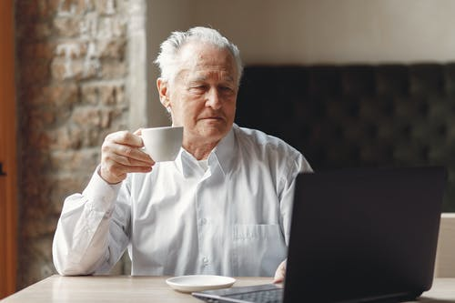 Focused elderly male enjoying cup of hot drink while surfing internet on laptop in creative modern office at daytime