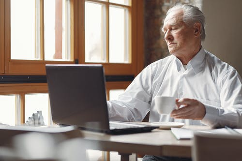 Relaxed aged man in smart casual outfit drinking hot drink and browsing netbook while working remotely in cafe at daytime