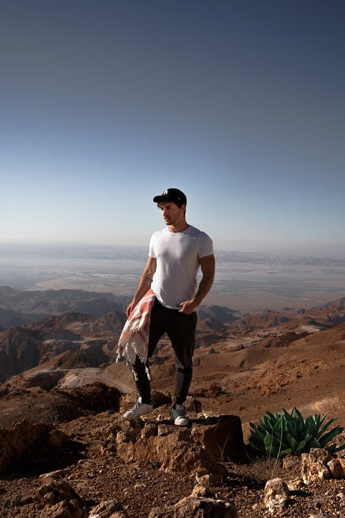 Man in White Crew Neck T-shirt and Black Pants Standing on Rock Formation