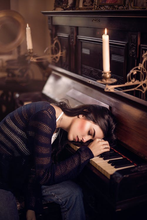 Woman in Black and White Sweater Lying on Piano