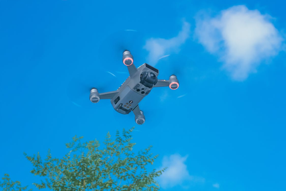 From below of modern UAV with photo camera and big propellers flying in sky above forest