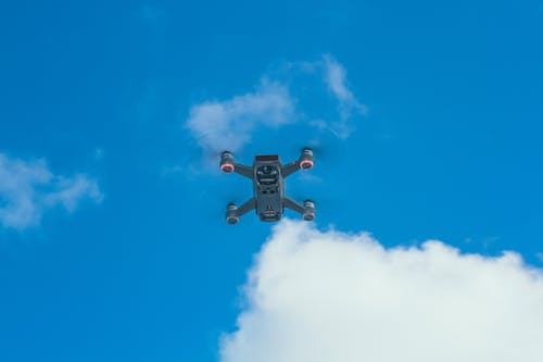 Drone flying past big cloud in sky