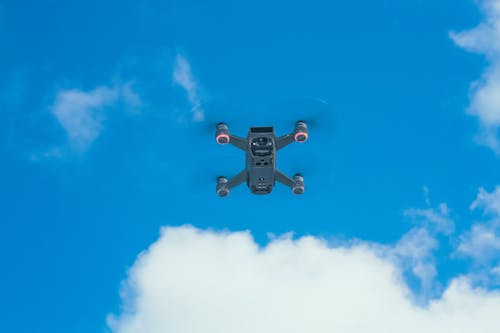 Modern UAV against blue sky with clouds