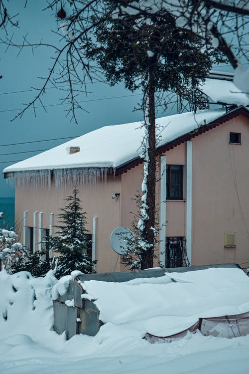 Small beige house with triangular roof covered with snow and icicles surrounded by wires and leafless trees in winter