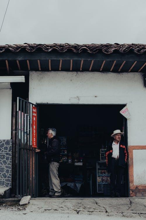 Senior men standing near entrance of store