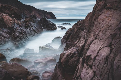 Dense fog above stones on coast of ocean