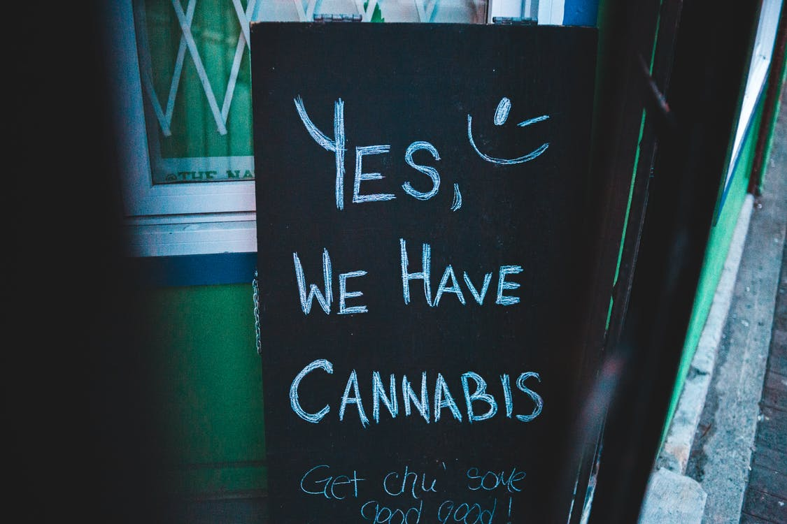 Lettering written on black chalkboard with cannabis offer near house on street of city