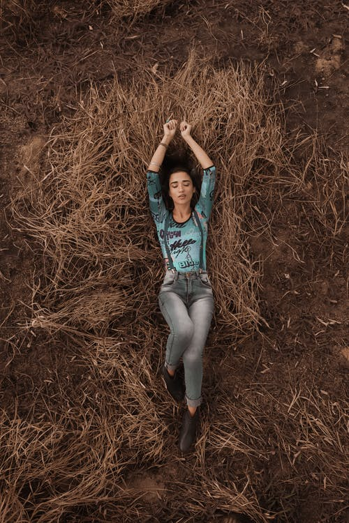 From above of calm woman with eyes closed wearing gray jeans relaxing on dry grass