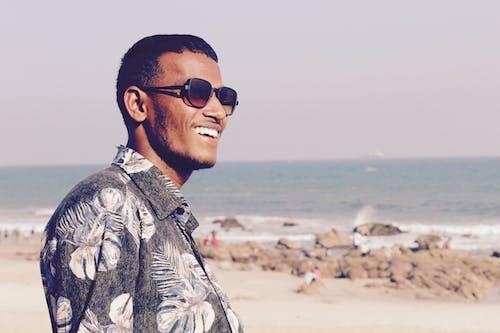 Cheerful ethnic man in sunglasses standing on beach