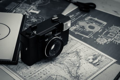 From above of black and white vintage film camera laced on table with map and notebook