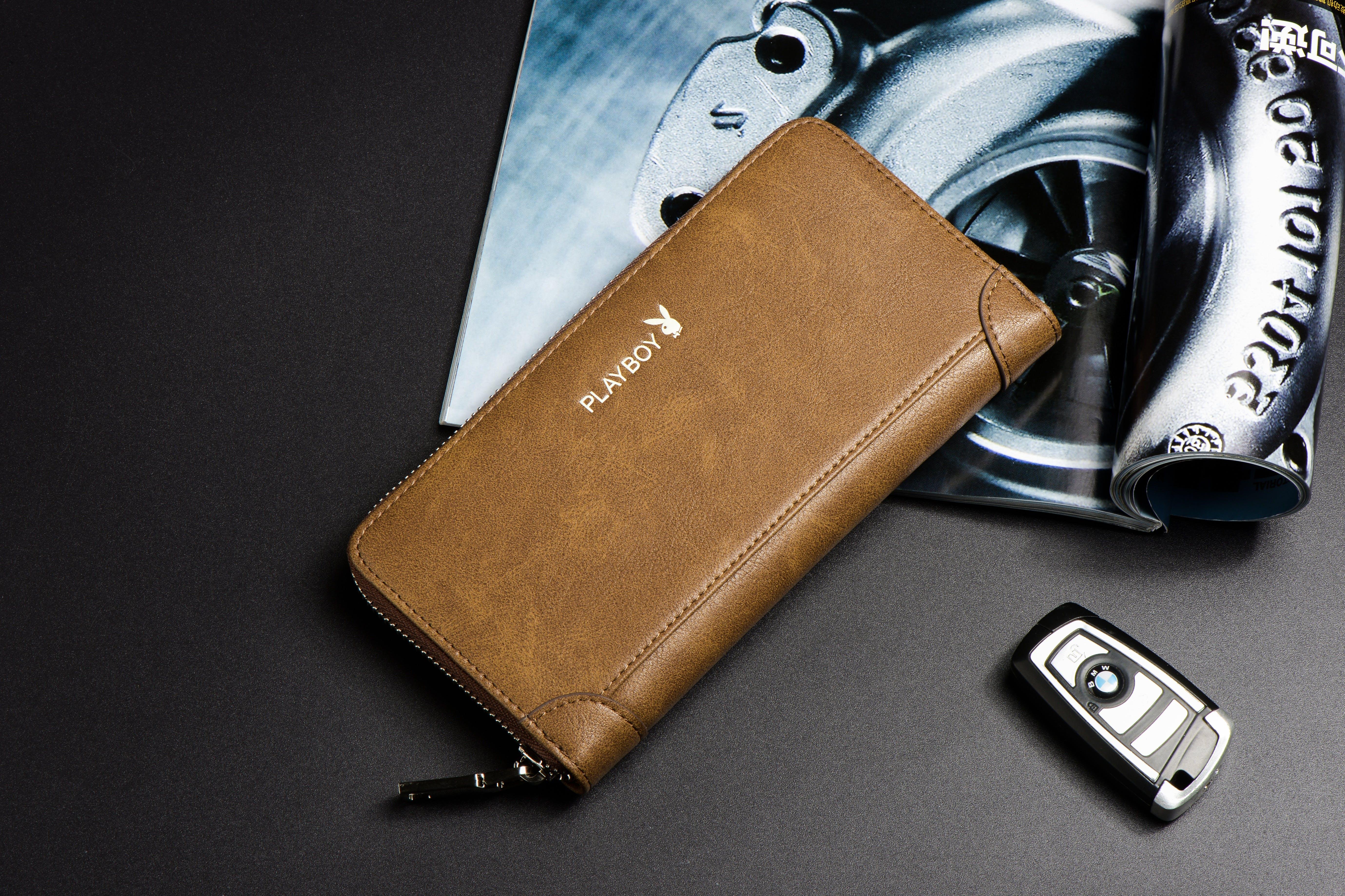 Brown Leather Wallet Beside Black Key Fob