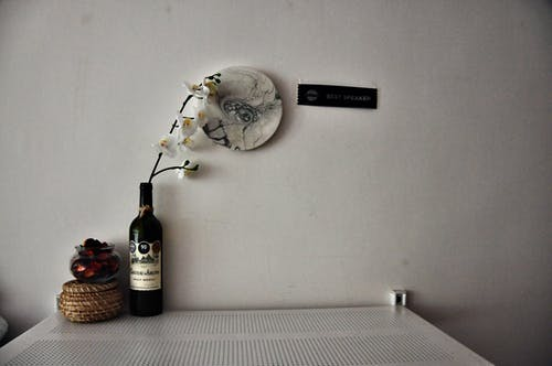 Composition with bottle with white flower placed near glass cup with dried petals