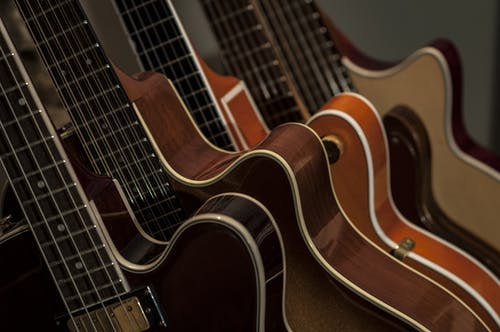 Shallow Focus Photography of Brown Guitars