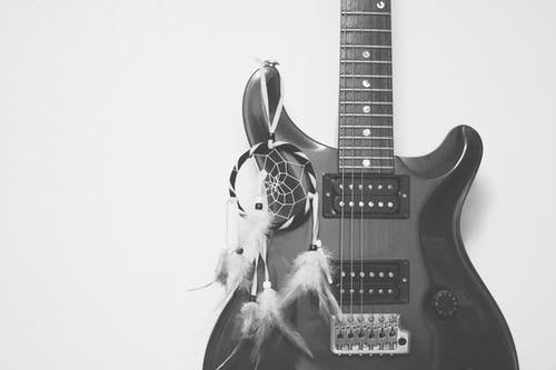 Grayscale Photography of Dreamcatcher Hanging on Electric Guitar