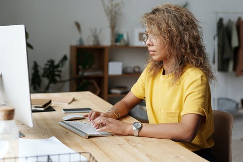 Woman in Yellow Crew Neck T-shirt Using White Laptop Computer
