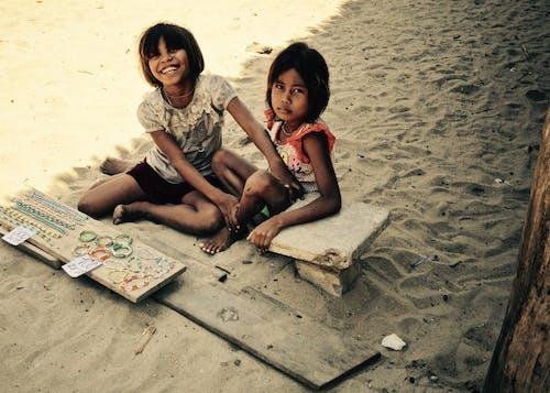 2 Girls Sitting on Sand
