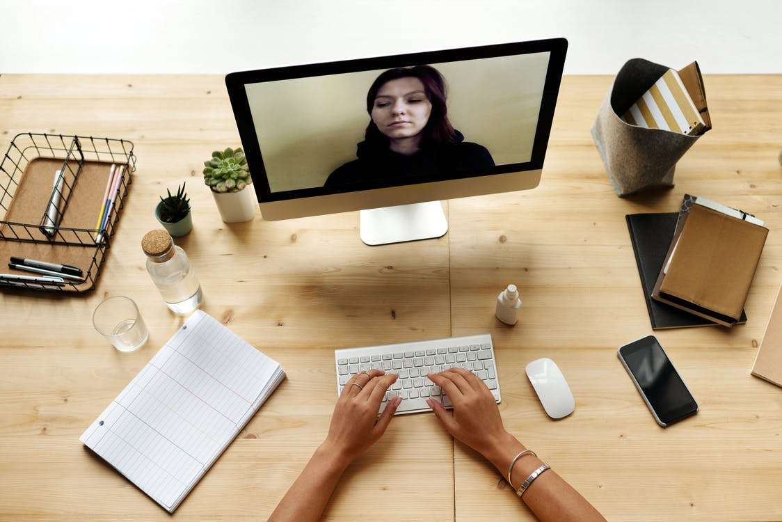 Woman in White Long Sleeve Shirt Using Silver Macbook