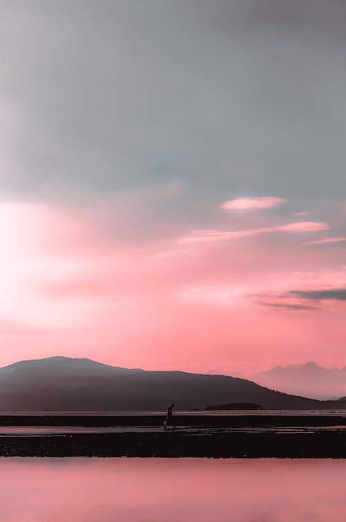 Unrecognizable tourist walking on stone pier near mountain at sunset