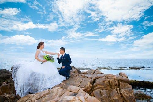 Newlywed couple on mount near sea on wedding day