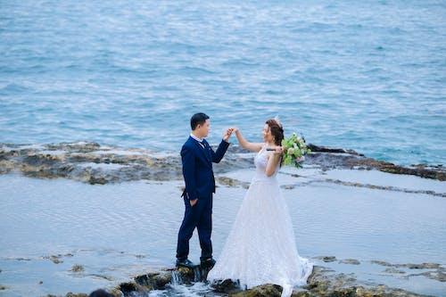 Elegant newlywed couple holding hands on mountain near sea