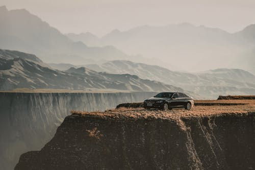 Modern car parked on cliff near mountains in foggy weather