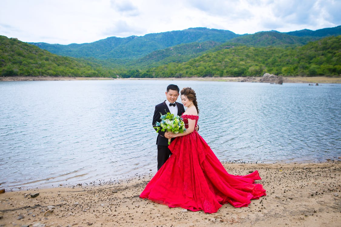 From above of smiling groom in suit embracing bride in red dress with flower bouquet while standing on sandy coast near lake and mounts under cloudy sky on wedding day