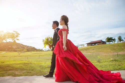 Side view of cheerful ethnic bride in colorful wedding dress strolling on walkway near groom with flower bouquet in rural zone with green hill and house under sky in sunlight