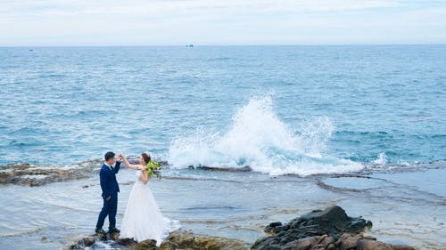From above side view of anonymous bride in wedding dress with flower bouquet holding hand of groom while standing near sea with splattering water and looking at each other