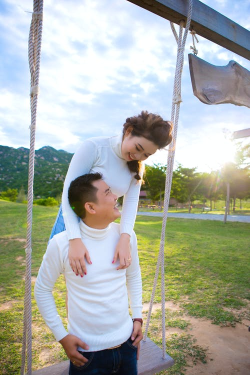 Cheerful Asian couple laughing on swing near green meadow