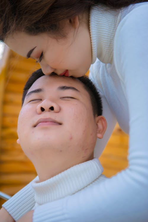 Side view of crop young ethnic female kissing gently and embracing dreamy male beloved in white knitted sweater with closed eyes while spending time together