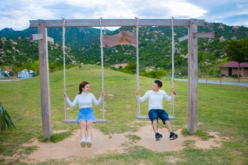Smiling young ethnic woman speaking with glad friend while sitting on wooden swings and looking at each other above grass lawn behind green ridge in summertime
