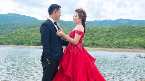 Elegant Asian couple embracing near lake on wedding day