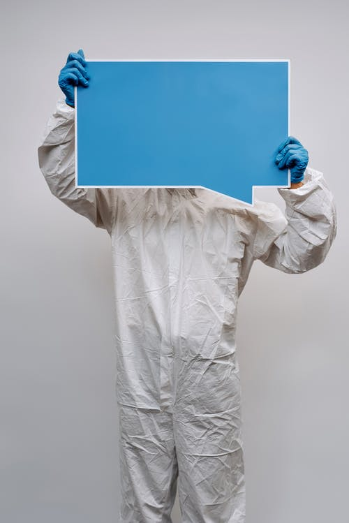 Person in White Long Sleeve Shirt Holding Blue Paper