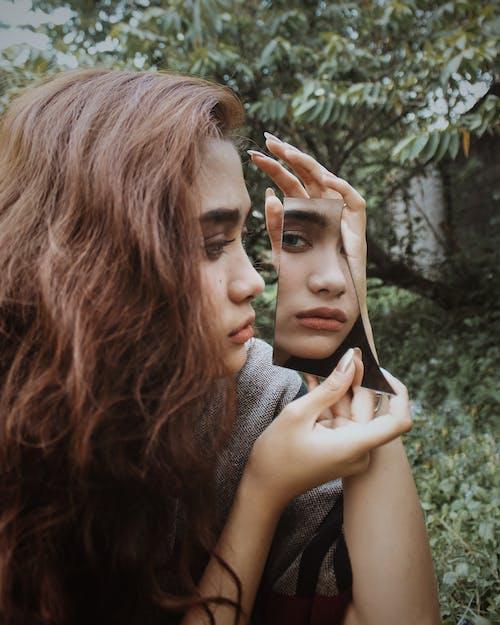 Close-Up Photo of Woman Looking at a Broken Mirror