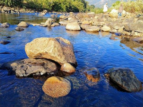 çakıl Taşları, çakıllar, kayalar yatağı, Mavi su içeren Ücretsiz stok fotoğraf