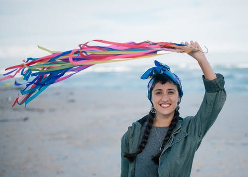 Cheerful ethnic female holding colorful ribbons up in wind
