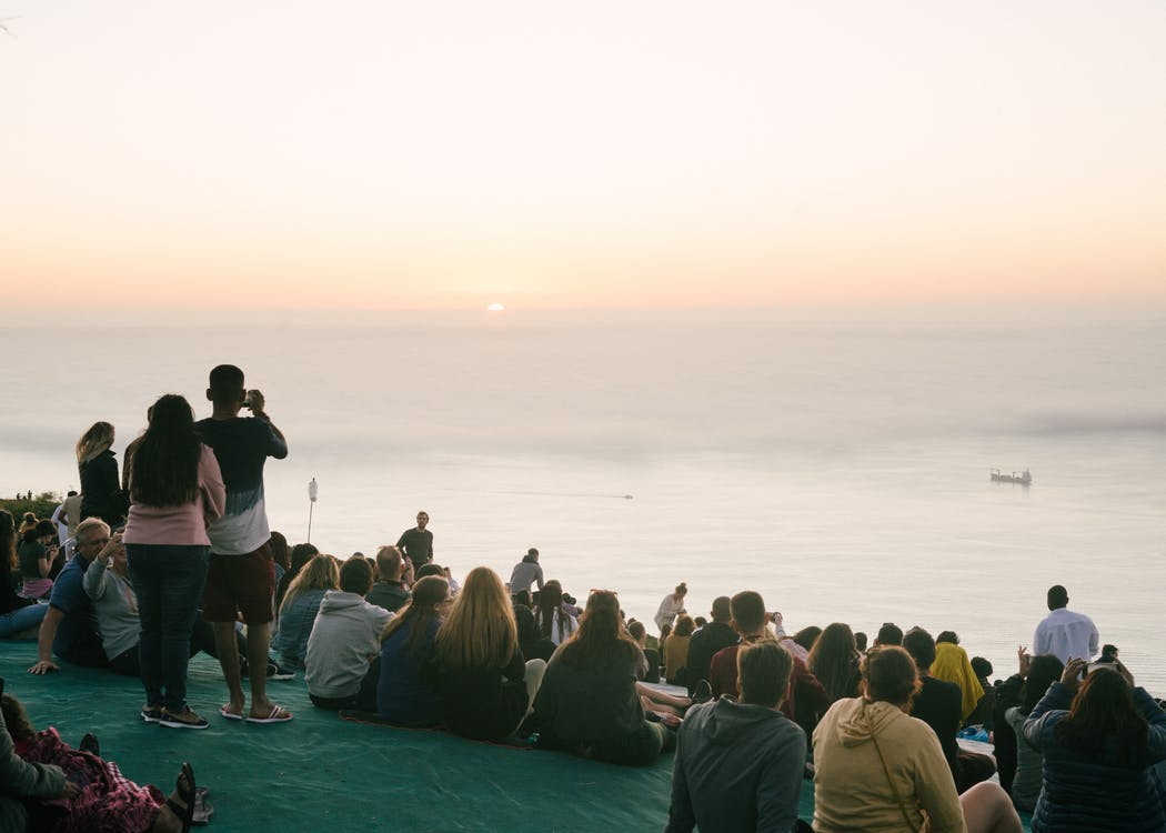 Back view of anonymous people enjoying seascape and sunset sitting on mountainside and taking photo