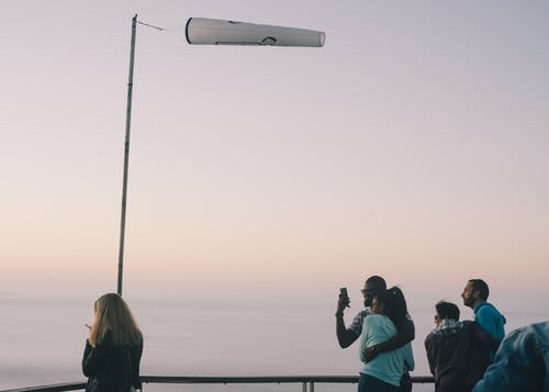 Tourists admiring sea view and sunset from observation platform