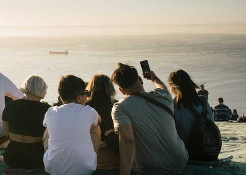 Back view of unrecognizable people in casual clothes sitting on mountainside and enjoying seascape and sunset while man and son taking selfie together