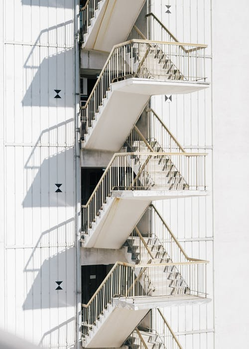 High stairway of contemporary stairway with metal railing of white wall of building in sunlight