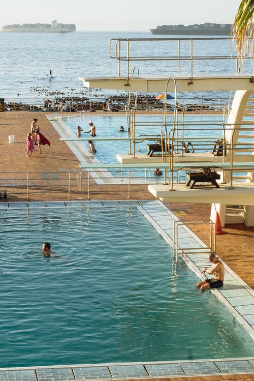 People swimming in pool near sea