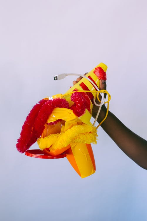 Crop black person demonstrating unsuitable plastic red and yellow traffic cone and tinsel and propeller hat and white and yellow usb wires and yellow duct tape on gray background