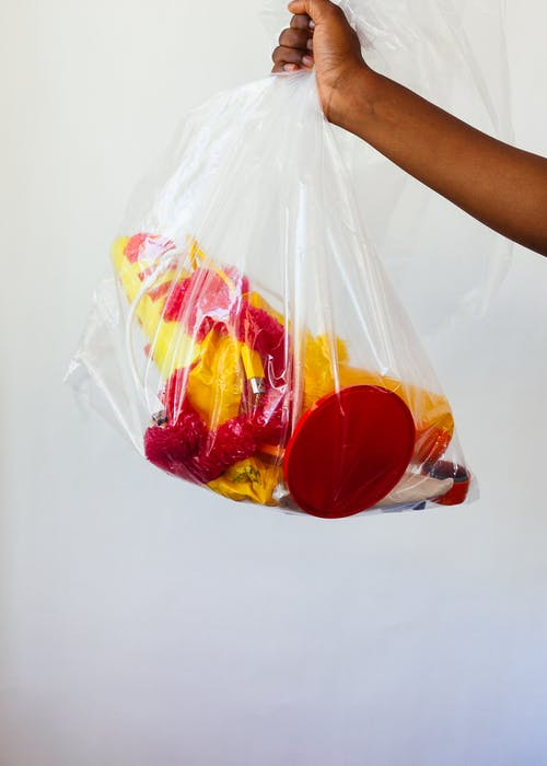 Crop black person demonstrating transparent plastic bag with yellow and red unsuitable plastic decoration and toys against gray background
