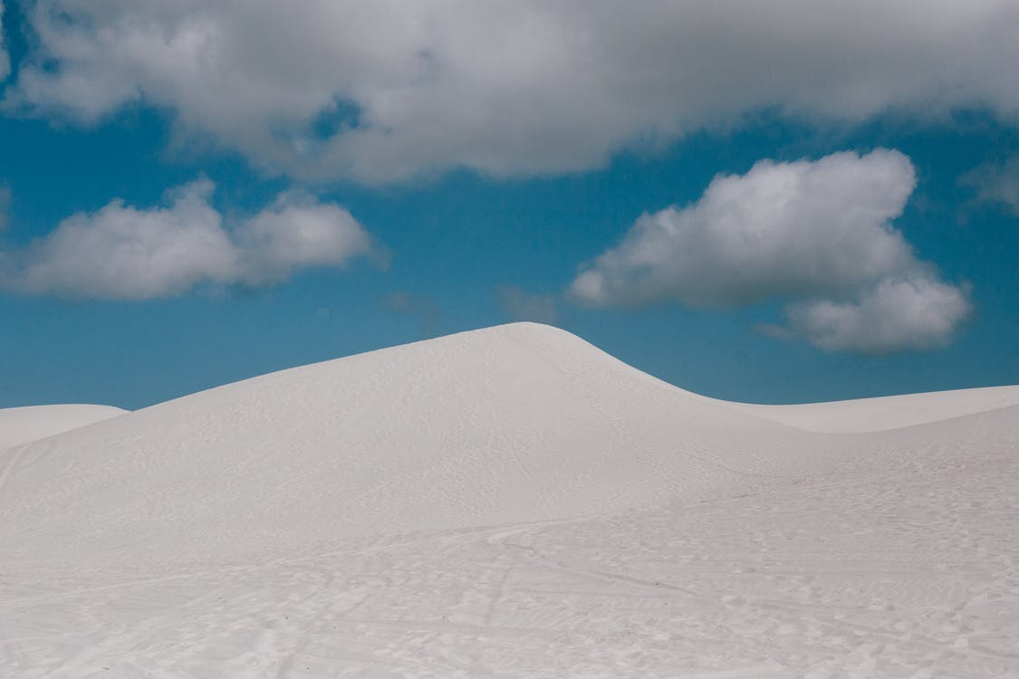 From below of pure blue sky with clouds over empty endless desert landscape with wheels and shoes tracks on surface