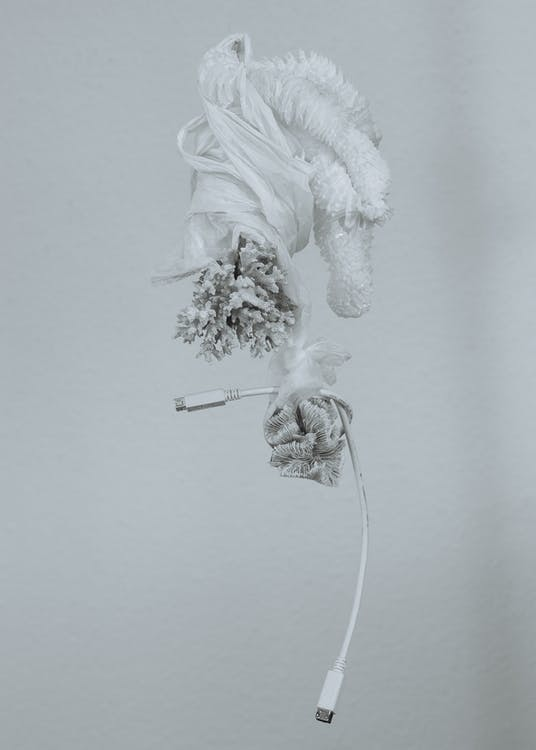 Concept of gray plastic Christmas toy with white unreal snow and white and gray tinsels and white USB wire bounded all together with by plastic bags on gray background
