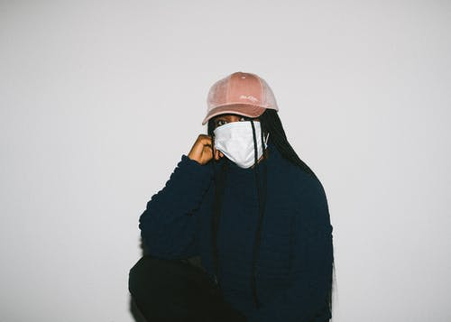 African American woman in medical mask on gray background