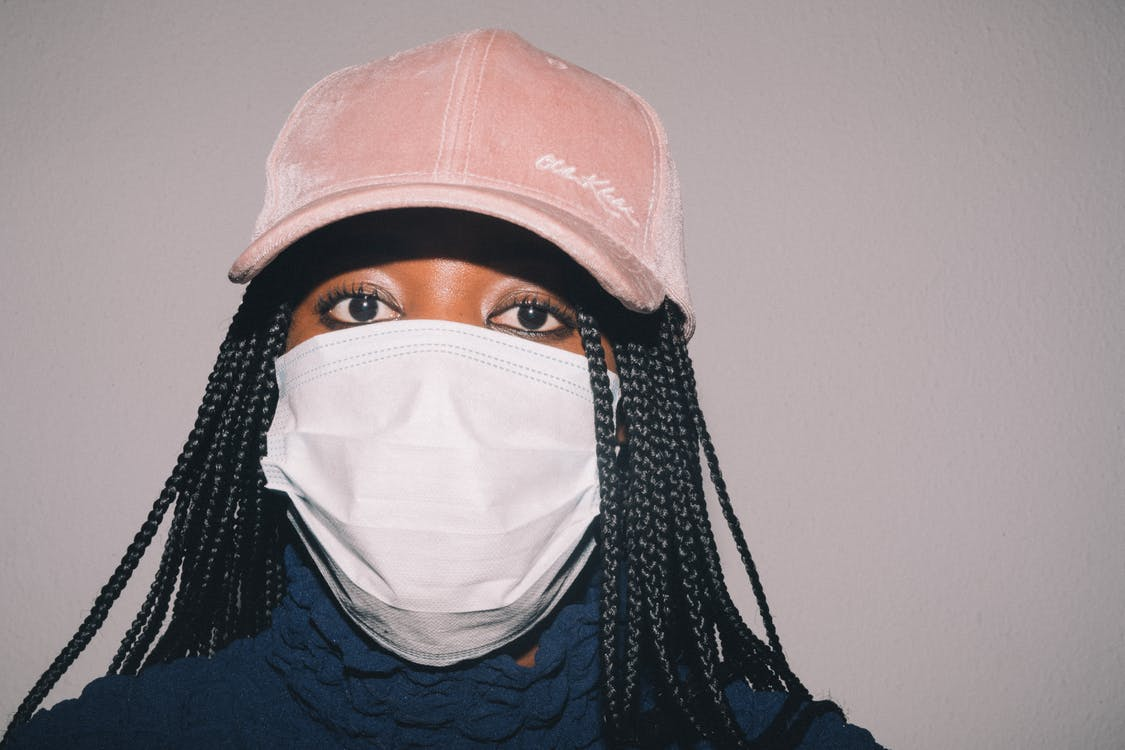 Adult African American woman in casual clothes and pink cap and medical mask while standing against gray background