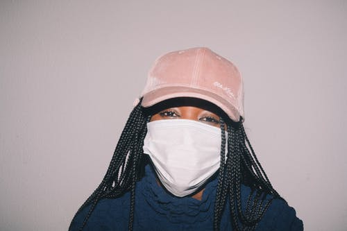 Black woman in medical mask on gray background