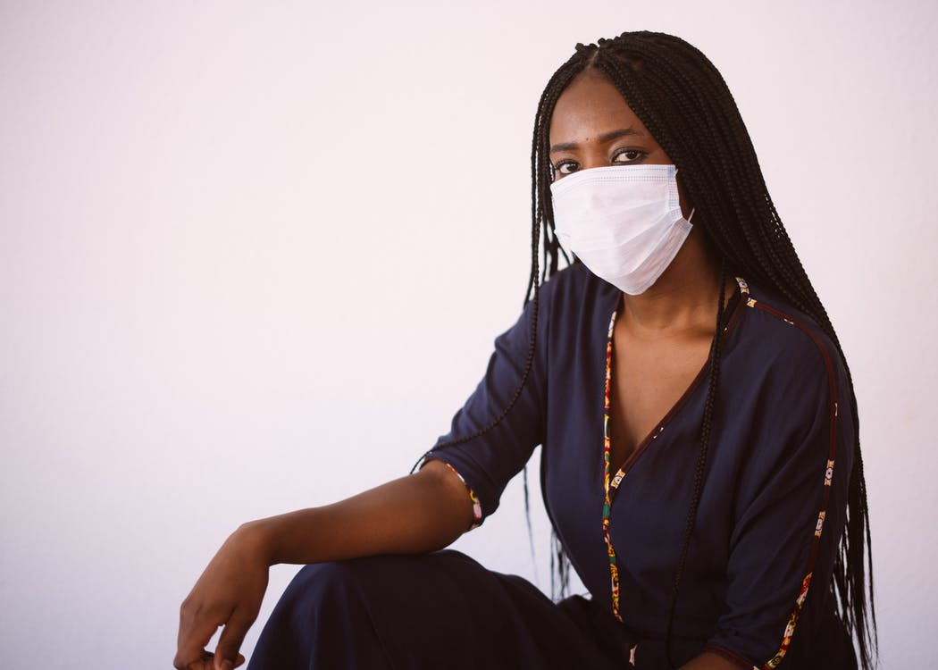 Side view of unrecognizable African American woman in casual dress and protective mask sitting against gray background looking at camera